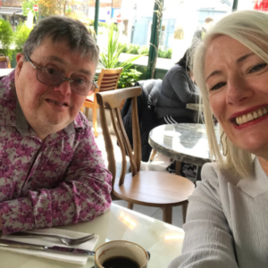 John and Aisling sit at a restaurant and smile at the camera